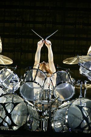 ドラムセットでXポーズをするyoshiki
